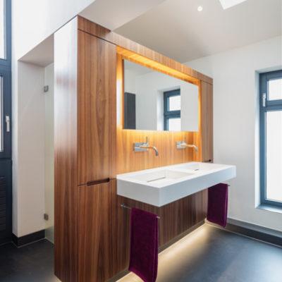 Badezimmer – Waschtisch vor Holz mit Unterlicht